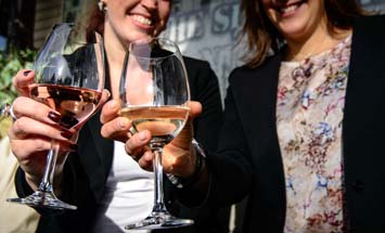 two women holding a glass of wine